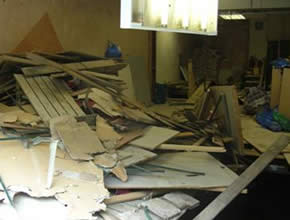 Photograph detailing the chaos inside the shop site, old materials piled messily next to a large, deep hole in the flooring.