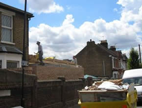 Man standing on an extension to the rear of a terraced house