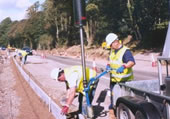 2 men laying a kerb down using a vacuum lifter