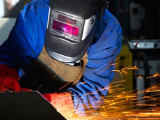 worker with protective mask and gloves welding
